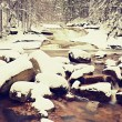Winter at mountain river. Big stones in stream covered with fresh powder snow and lazy water with low level. Reflections of forest in water level. — Stock Photo #63798633