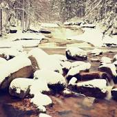 Winter at mountain river. Big stones in stream covered with fresh powder snow and lazy water with low level. Reflections of forest in water level. — Stock fotografie