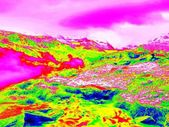 Alpine spring mountain path in infrared photo. Hilly landscape in background. Sunny weather with clear sky above. Amazing thermography colors. — Stock Photo