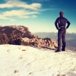 Tourist in winning poza is standing on snowy view point. National park Alps park in Italy. Sunny winter morning. — Stock Photo #66837045