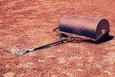 Old rusty iron barrel for maintenance of neglect tennis court. Old dry red crushed bricks surface on outdoor tennis ground. Retro filter — Stock Photo