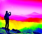 Fantastic infrared scan. Tourist with poles stand on rocky view point and watching into misty morning landscape. Melancholic autumn morning. Thermography colors — Stock Photo