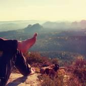 在黑暗的远足长裤裸男毛腿休息一下以上谷岩峰上. — 图库照片