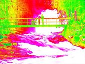 Foamy water of waterfall, bellow footpath bridge with people. Cold water of mountain river in infrared photo. Amazing thermography.  — Stock Photo