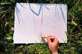 Close up view of child's hand drawing colorful ornaments on paper. Notebook in fresh green grass of meadow. — Stock Photo