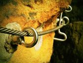Rock climbing safety path via ferrata. Steel chrome anchores in rock hold steel twisted rope — Stock Photo