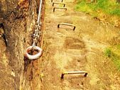 Rock climbing safety path via ferrata. Steel chrome anchores in rock hold steel rope — Stock Photo