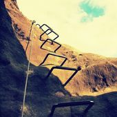 Climbers way. Iron twisted rope fixed in block by screws snap hooks. The rope end anchored into sandstone rock. — Stock Photo
