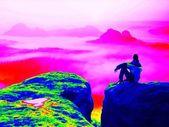 Fantastic infrared scan. Tired tourist on the rocky peak. Wonderful daybreak in mountains, heavy orange mist in deep valle — Stock Photo
