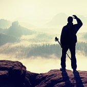 Misty day in rocky mountains. Silhouette of tourist with poles in hand. Hiker stand on rocky view point above misty valley. — Stock Photo