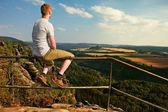 Ginger man sit on handrail at peak of rock and watch to landscape.  Sunny day in rocky mountains. Hiker with grey shirt, pants and boots. — Stock Photo