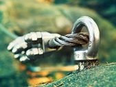 Detail of steel bolt anchor eye in rock. The end knot  of steel rope. Climbers path in rocks via ferrata. Iron twisted rope fixed in block. — Stock Photo