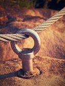 Detail of steel bolt anchor eye in sandstone rock. The end knot  of steel rope. Climbers path via ferrata. Iron twisted rope fixed in block. — Stock Photo