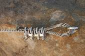 Solid knot on steel rope. Iron twisted rope fixed in block by screws snap hooks. Detail of rope end anchored into sandstone rock — Stock Photo