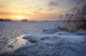 Beautiful winter landscape with frozen lake and sunset sky. — Stock Photo