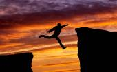 Man jumping across the gap from one rock to cling to the other. — Stock Photo