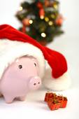 Part of piggy bank with Santa Claus hat and three little gifts and  shining christmas tree standing on white background — Stock Photo