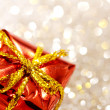 Christmas red gift box with yellow bow on glitter silver and gold background — Stock Photo #52284287