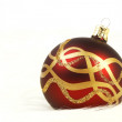 Red and gold christmas ball on white fur background — Stock Photo #53001645