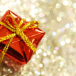 Christmas red gift box with yellow bow on glitter silver and gold background — Stock Photo #53068179