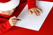 Christmas helper child writing letter to Santa Claus letter in red hat — Stock Photo