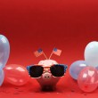 Piggy bank with retro sunglasses with USA flag and blue, red and white party balloons and two small USA flags on red background — Stock Photo #68915553