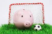 Pink piggy bank with football ball on green field with gate on white background — Stock Photo