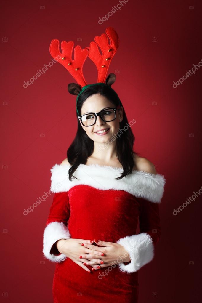 mujer joven feliz con ropa de santa claus y traje de reno sobre fondo rojo u