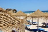 Straw umbrellas on a beach — Stock Photo