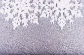 White snowflakes on a background of silver sequins — Stock Photo