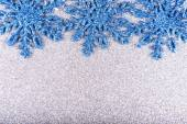 Blue snowflakes on a background of silver sequins — Stock Photo