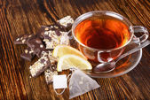 Cup of tea with lemon on wooden background — Stockfoto