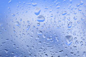 Look at the blue sky through the window with raindrops — Stock Photo