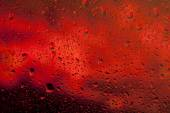 Look at the bright red fire through the glass with raindrops — Stock Photo