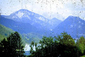 View of the mountains through the glass with raindrops — Stock Photo