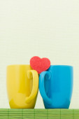 Two color cups and heart — Stock Photo