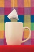 The tea bag hangs over a cup — Stock Photo