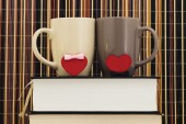 Two cups with hearts on books — Stock Photo