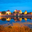 Malbork castle by night with reflection in Nogat river — Stock Photo #54758959