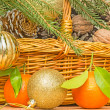 Christmas balls and tangerines on a background of a basket with — Stock Photo #51868339