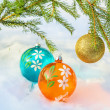 Three multicolored Christmas balls and fir branch — Stock Photo #57851829