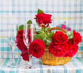 Red roses in a basket and two glasses — Stock Photo