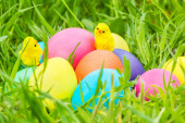 Toy chicks on Easter eggs in the grass — Stock Photo