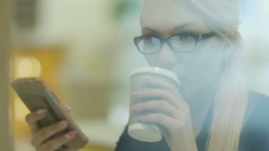 Woman Drinking Coffee While Using Mobile Phone in Caffee — Stock Video