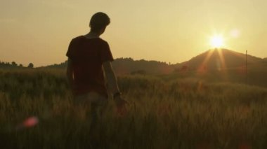 Young Man Walking and Raising Hands in the Wheat Field at Sunset Time — Vídeo stock