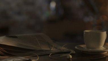 Taza de café y periódico en la mesa en la luz del sol mañana. — Vídeo de Stock