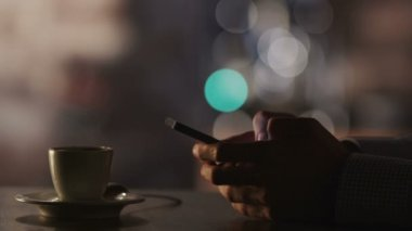 Man Typing a Message Using Mobile Phone at Evening Time in Coffee House. — Stock Video