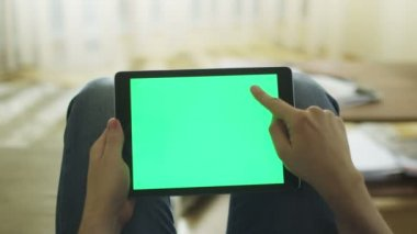 Man is Laying on Couch at Home and Using Tablet with Green Screen in Landscape Mode on Lap — Stok video