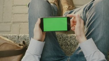 Man is Using Phone in Landscape Mode on Lap Outdoors at Sunny Day. POV — Stok video