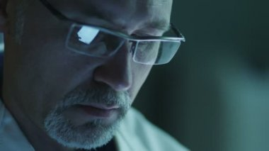 Portrait of Middle Aged Male using Tablet and Have Reflections of Screen in Glasses. Close-up. — Stock video